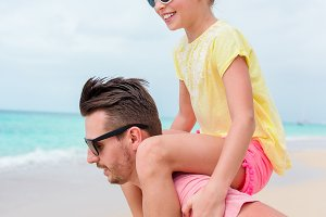 Happy dad and his little daughter at tropical beach having fun