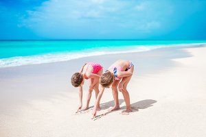 Happy little girls play with sand on the beach. Two kids making sand castle with white sand