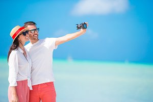 Selfie couple taking photos on the beach. Tourists people taking travel photos on summer holidays.