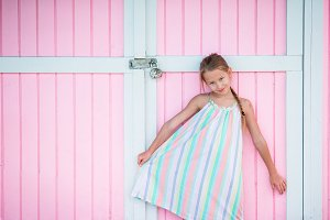 Adorable little girl outdoors near traditional caribbean colorful pink house