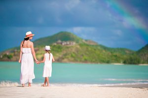 Beautiful mother and daughter on Caribbean beach with amazing rainbow on background