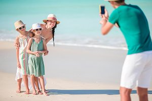 Man taking a photo of his family on the beach. Family beach vacation