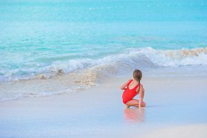 Adorable little girl on the beach in shallow water