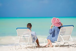 Happy couple relaxing on a tropical beach on sunbed