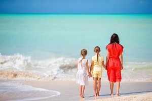Beautiful mother and her adorable little daughters at beach