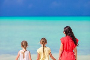 Beautiful mother and her adorable little kids at beach