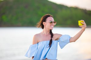 Beautiful young woman taking a self photo herself on tropical beach