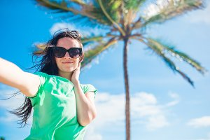 Young woman taking selfie portrait background palm tree on the beach