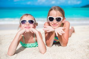 Adorable little sisters at beach during summer vacation lying on warm sand. Portrait of kids on white beach