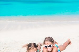 Adorable little sisters at beach during summer vacation lying on warm sand