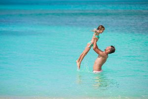 Happy family of dad and kid playing in the sea