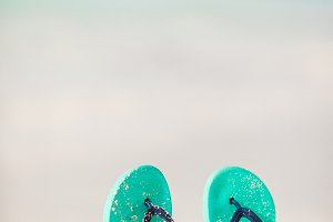 Summer mint flip flops with sunglasses on white beach
