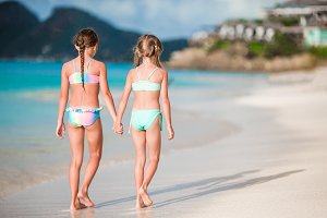 Kids having fun at tropical beach during summer vacation playing together. Little girls running in shallow water