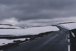 Dark Road over the Mountains in Snow