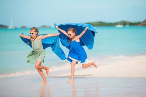 Little girls having fun at tropical beach playing together. Adorable little sisters at beach during summer vacation