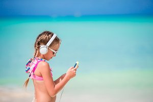 Little adorable girl listening music by cellphone on the beach