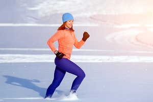 Woman runs through the winter snow