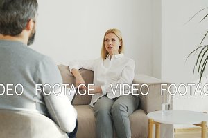 Adult stressed woman with depression talking with male professional psychoanalyst in psychotherapy office indoors