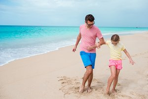 Family fun on white sand. Smiling father and adorable child playing on the beach