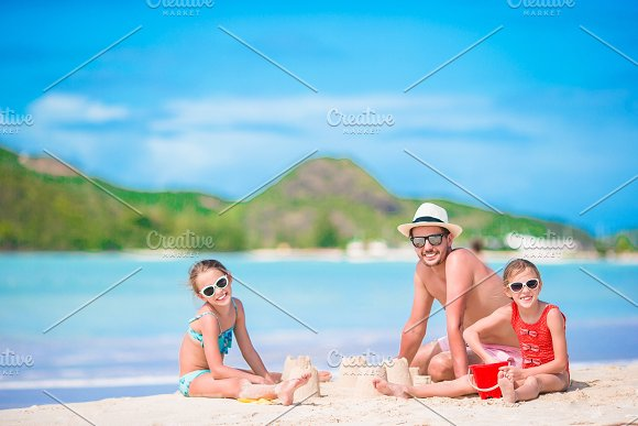 Family Making Sand Castle At Tropical White Beach