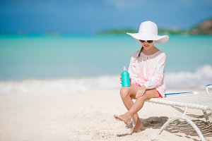 Little girl in hat with bottle of sun cream sitting at tropical beach