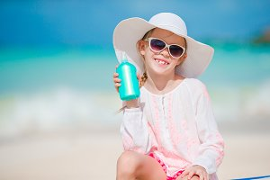 Little girl in hat with bottle of sun cream sitting at sunbed on tropical beach