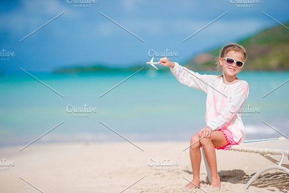 Happy Little Girl With Toy Airplane In Hands On White Sandy Beach Kid Play With Toy On The Beach