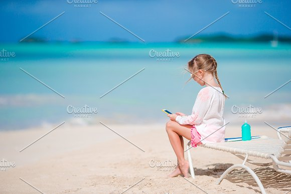 Little Girl Playing With By Her Smart Phone Sitting On The Sunbed