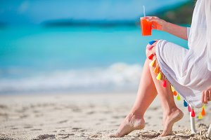 Young woman with cocktail glass on white beach sitting on sunbed. Closeup tasty cocktail background the sea