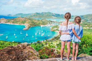 Little kids with beautiful famous view. View of English Harbor from Shirley Heights, Antigua, paradise bay at tropical island in the Caribbean Sea