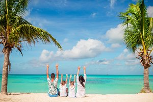Happy family on beach vacation raised their hands