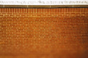 Brick wall texture with snow on top of it background