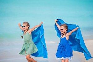 Little cute girls having fun on white beach