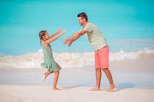 Happy father and his adorable little kid at tropical beach having fun