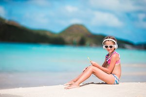 Little adorable girl on the beach listening the music in big headphones