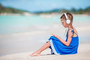 Little adorable girl on the beach listening the music