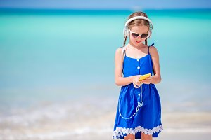 Little adorable girl listening music background sea sitting on the sand