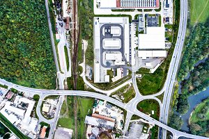 Aerial view of industrial buildings, highway and little town