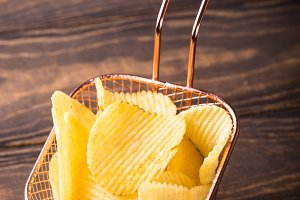 Crispy potato chips in copper basket