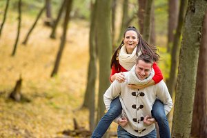 Couple in love, man giving his woman piggyback