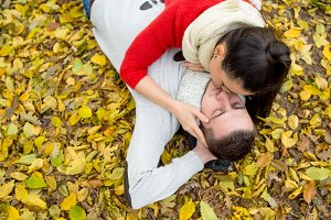 Beautiful couple in autumn park lying on the ground