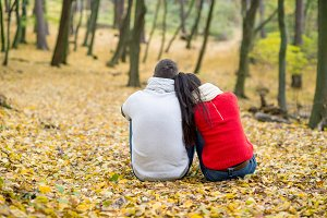 Beautiful couple in autumn park sitting on the ground