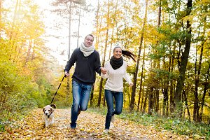 Beautiful young couple with dog running in autumn forest