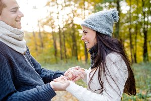 Beautiful young couple holding hands. Sunny autumn nature.