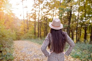 Beautiful woman in checked coat and hat, autumn forest
