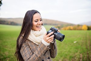 Beautiful young woman with camera taking pictures. Autumn nature