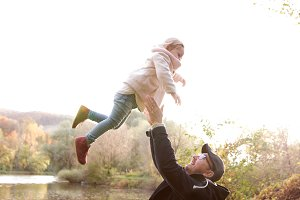Father holding little daughter, throwing her in the air