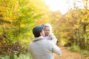 Father holding little daughter in his arms. Autumn nature.