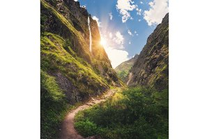 Mountains covered green grass, high waterfall at sunset