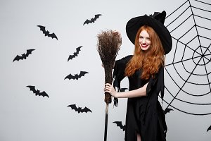 Halloween Witch Concept - Portrait of beautiful young witch with broomstick over grey wall with bat and spider web background.